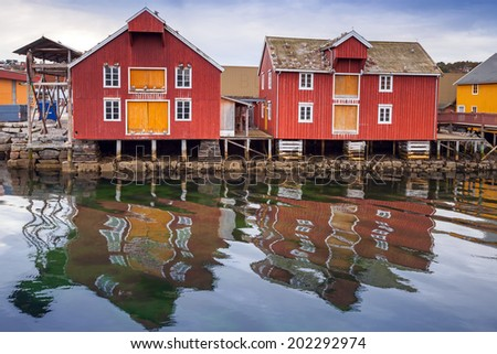 Red and yellow wooden houses in Norwegian fishing village - stock photo