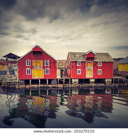 Red and yellow wooden houses in Norwegian fishing village. Instagram toned effect - stock photo