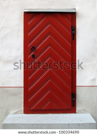 Red antique wooden door with metal handle and white plaster wall around - stock photo