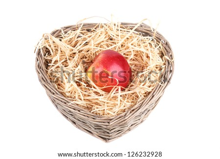 red appl in the basket with sawdust