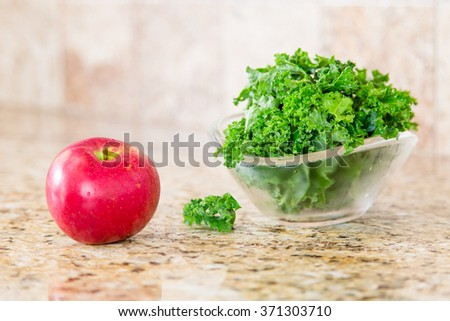 Red apple and a bowl of fresh green kale in a glass bowl on a granite counter top.