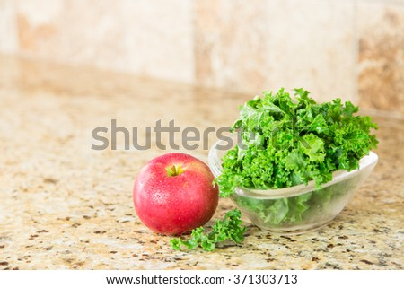 Red apple and a bowl of fresh green kale in a glass bowl on a granite counter top. Copy space.