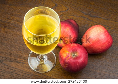 red apple and apple juice on wooden background