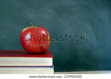 red apple and books in classroom - stock photo