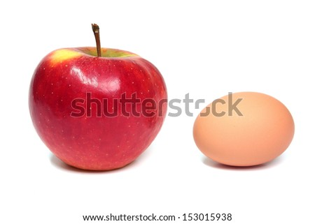 Red apple and brown egg on a white background. - stock photo
