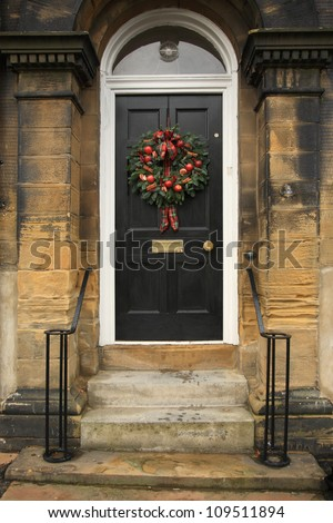 Red apple and chillies Christmas wreath on a black door - stock photo