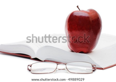 Red apple and glasses on the book - stock photo
