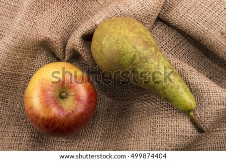 red apple and green pear on brown jute