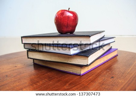 red apple and  old books  on wooden tabletop