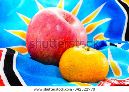 Red apple and orange on blurry colorful batik cloth background:Close up,select focus with shallow depth of field - stock photo