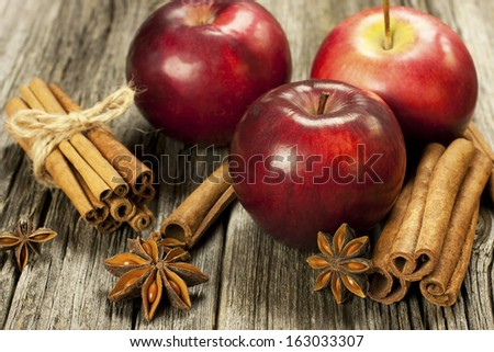 red apple and spices on a wooden surface