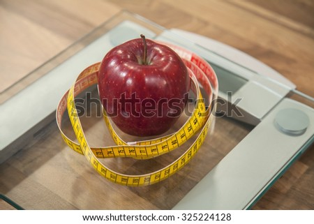 Red apple and yellow measuring tape on weight scale. Dieting concept. - stock photo