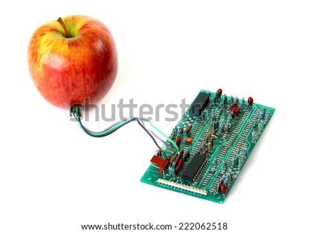 Red apple connected to the electric board isolated over white background - stock photo