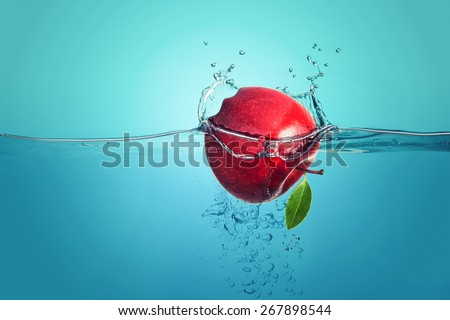 red apple falling into water splach - stock photo