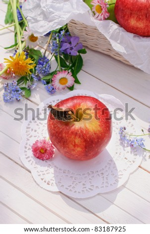 Red apple, flowers and basket on white garden table in sunny summer day - stock photo