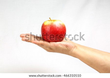 Red apple held on hand finger on white background