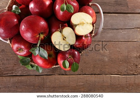 Red apple in wicker basket on wooden table, top view