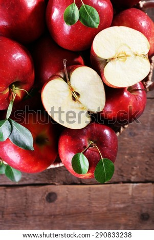Red apple in wicker basket on wooden table, top view - stock photo