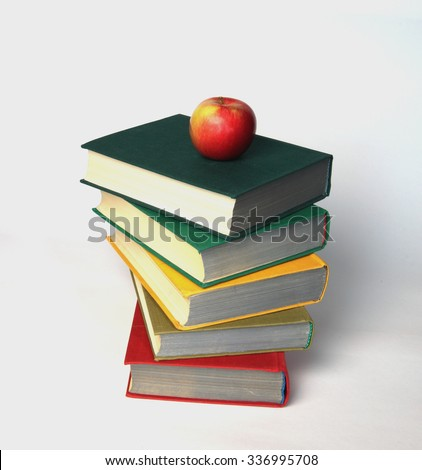 Red apple on a Stack of old books on white as a symbol of education and knowledge - stock photo