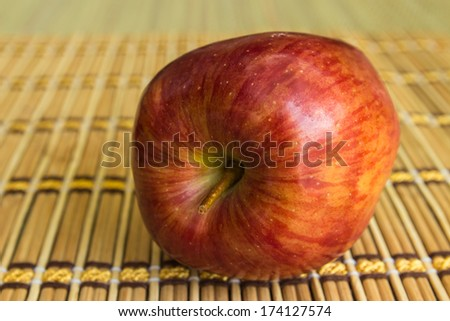 Red apple on bamboo brown straw mat background - stock photo