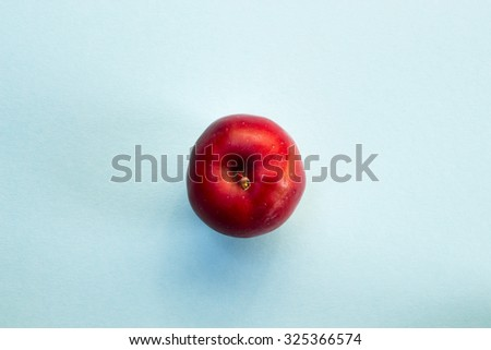 Red apple on blue background, shot from above - stock photo