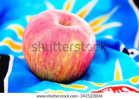 Red apple on blurry colorful batik cloth background:Close up,select focus with shallow depth of field - stock photo