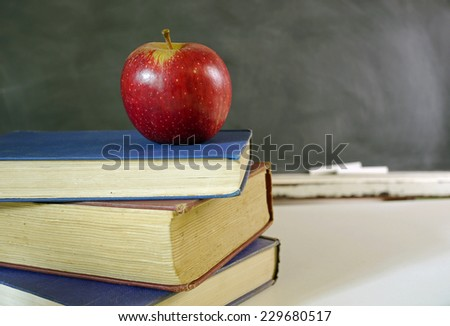 Red apple on books in classroom
