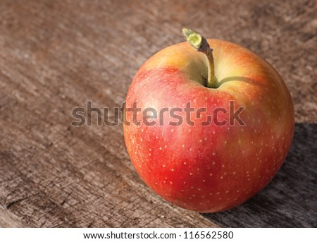 Red apple on old wooden table from above, with copy space. - stock photo