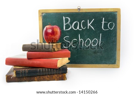 red apple on pile of old retro books in front of an old blackboard - stock photo