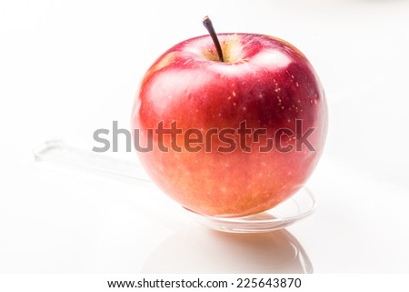 red apple on translucent medicine spoon on the table symbolizing that drinking and eating of apple products prevents diseases and is full of vitamins