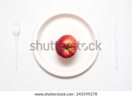 Red apple on white plate with knife and fork, - stock photo