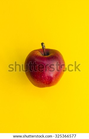 Red apple on yellow background