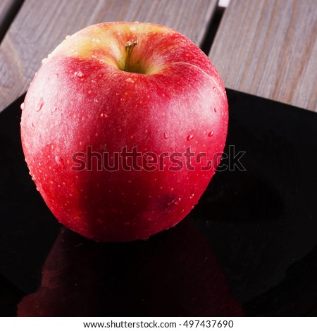 Red apple over black plate, square image