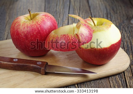 Red apple peeled and knife on old wooden table - stock photo