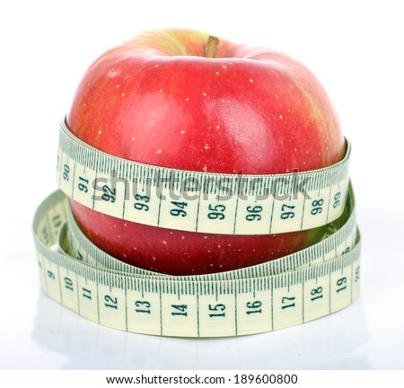 Red apple . Red apple wrapped in a tailor's tape measure on a white background