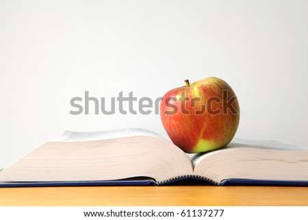 Red apple resting on an open book