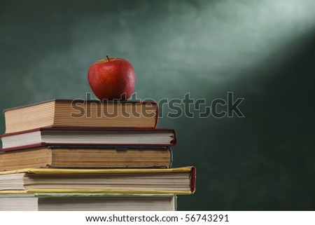 red apple resting on the book with chalk board as background