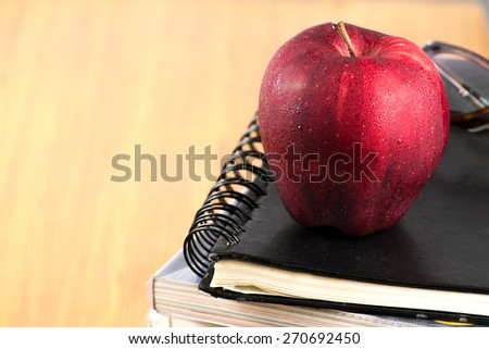red apple resting on the book  with glasses  - stock photo