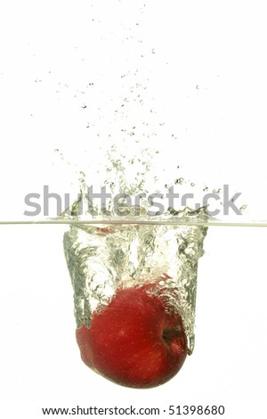 Red apple splashing in water in white background