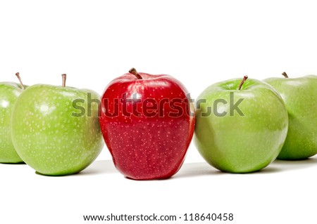 Red Apple Standing In Center Of Green Apples Being Different