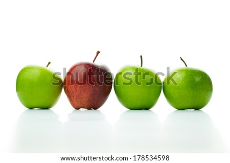 Red apple standing out in a row of green apples - stock photo