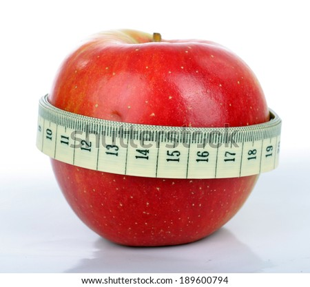 Red apple with a tape measure . Red apple wrapped in a tailor's tape measure on a white background