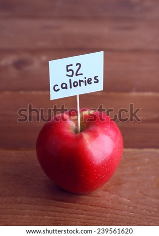 Red apple with calories count label on wooden table background - stock photo