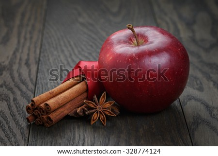 red apple with cinnamon sticks and anise on wooden table