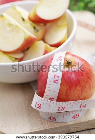 Red apple with measuring tape on the wooden table. Diet concept.