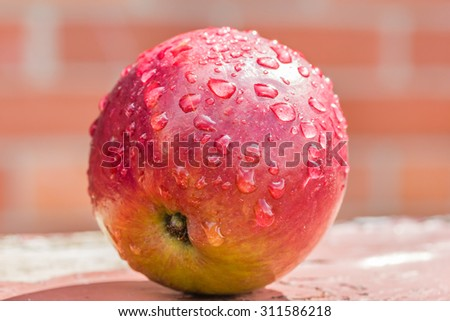 Red apple with water drops close-up on background blurred brick wall. Selective focus - stock photo