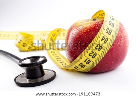 Red apple with water drops yellow measuring tape and black stethoscope isolated on white