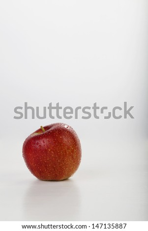 red apple with waterdrop on white background, with selective focus. Space for text.