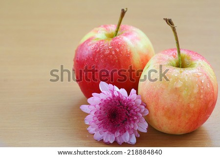 Red apples and  Chrysanthemum on the wooden table, close up - stock photo