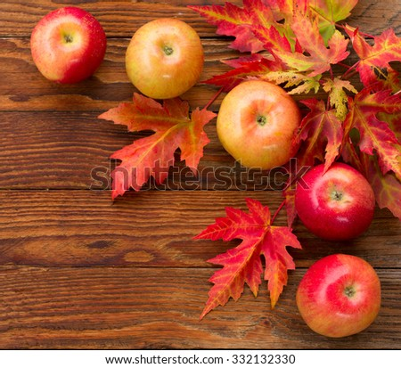 red apples and colorful autumn leaves of maple on a wooden background. square photo, top view. autumn concept
